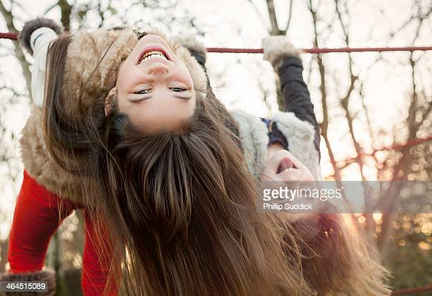 Two happy girls swinging upside down on rope