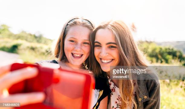 Two happy girls taking a selfie outdoors
