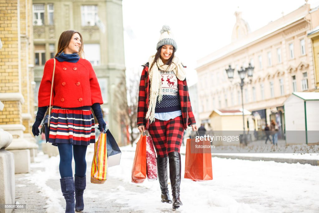 Two happy girls walking down the street : Stock Photo