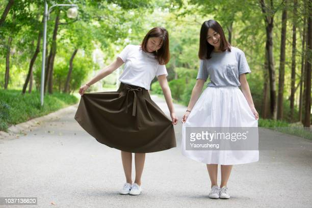 two happy girls wearing black and white skirts in the park,full body portraits - jupe vent photos et images de collection