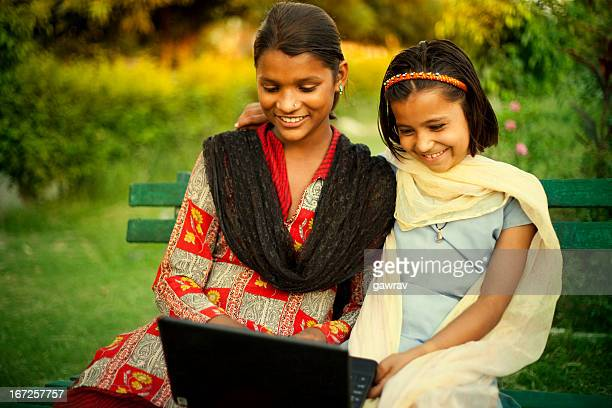 Two happy Indian girls using laptop in park