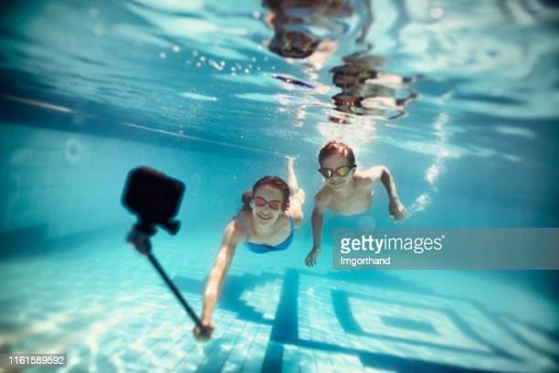 Two happy kids filming themselves with underwater camera
