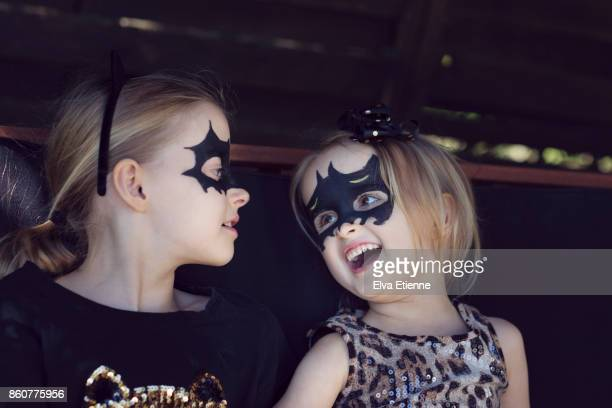 Two happy, laughing children with bat shaped face paints