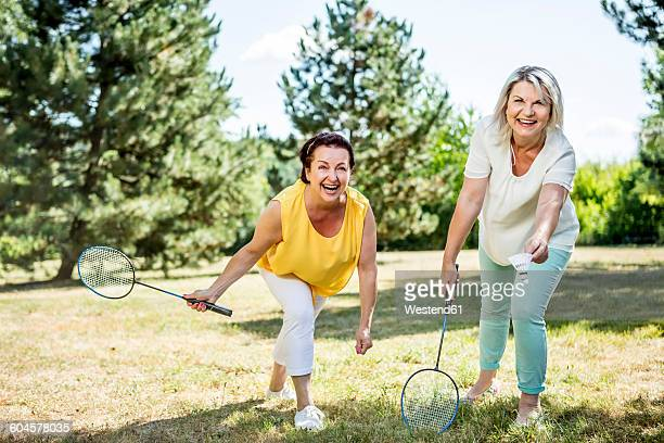 two happy mature women on a meadow playing badminton - badminton stock pictures, royalty-free photos & images