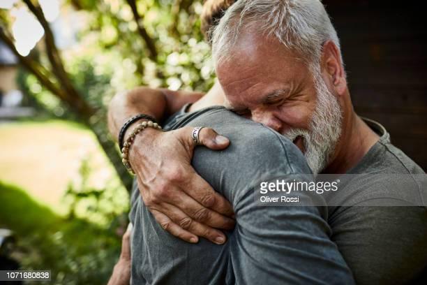 two happy men embracing at garden shed - einfaches leben stock-fotos und bilder