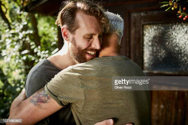 two happy men embracing at garden shed - embracing stock pictures, royalty-free photos & images