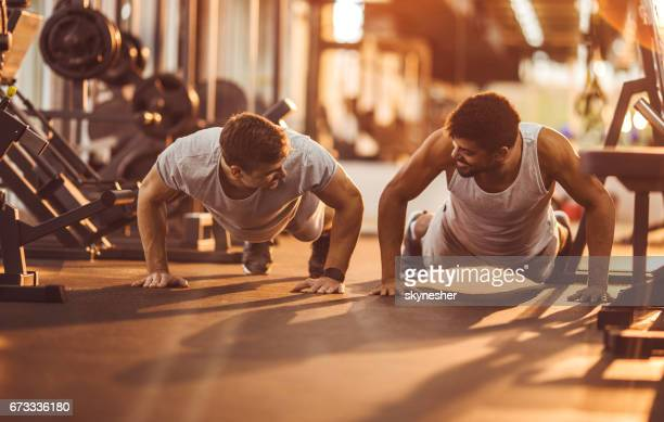 Two happy men exercising push-ups in a health club.