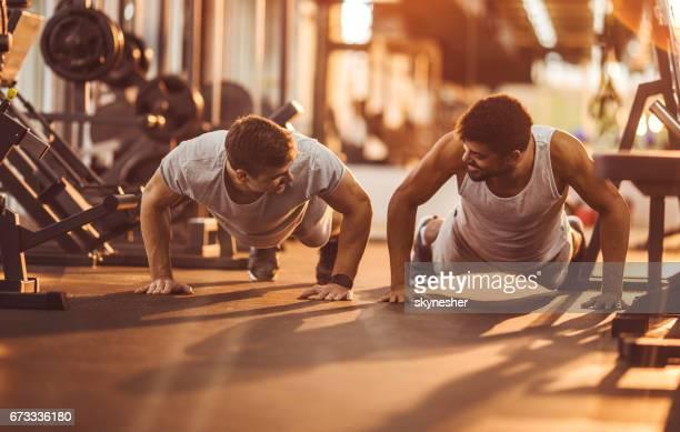 Zwei glückliche Männer Liegestütze in einem Fitnessstudio trainieren.