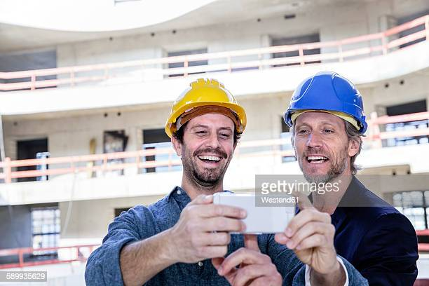 Two happy men on construction looking at cell phone