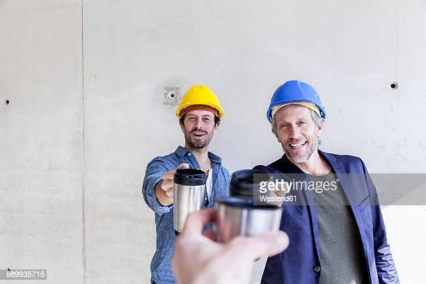 Two happy men on construction site toasting with mugs