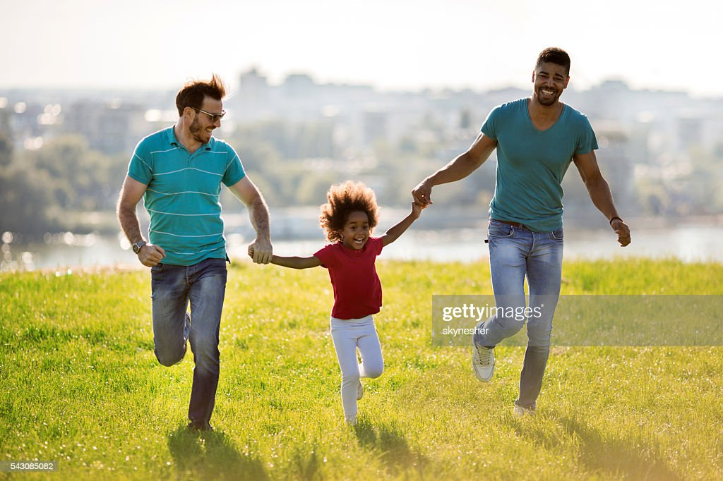 Two happy men running with African American little girl outdoors. : Stock Photo
