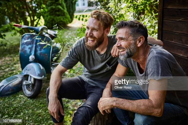 two happy men sitting together at garden shed with old motor scooter in background - mid adult men stock pictures, royalty-free photos & images