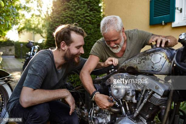 two happy men with motorcycle in garden - hobbies stock pictures, royalty-free photos & images