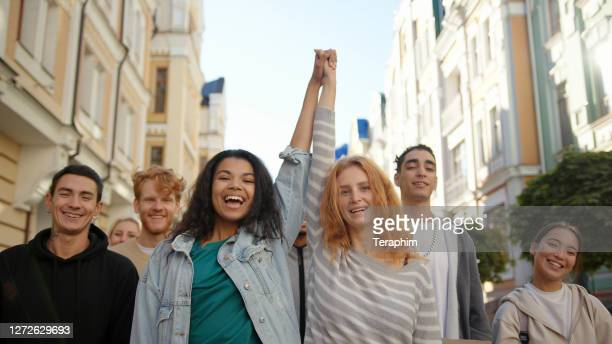 two happy mixed race women lift hands up together in a mass protest against racism - marching stock pictures, royalty-free photos & images