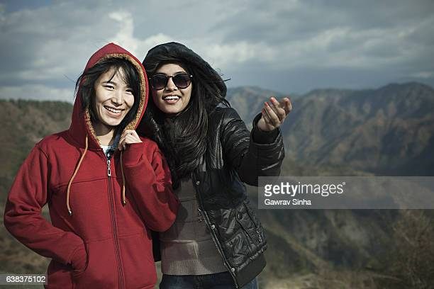 Two happy multi ethnic Asian female friends in mountains.