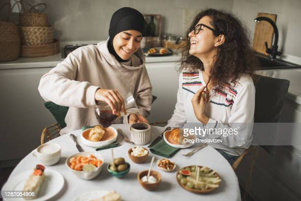 two happy multiracial girls having breakfast and drinking coffee at home together. multicultural friendship. one in hijab. - female friendship stock pictures, royalty-free photos & images
