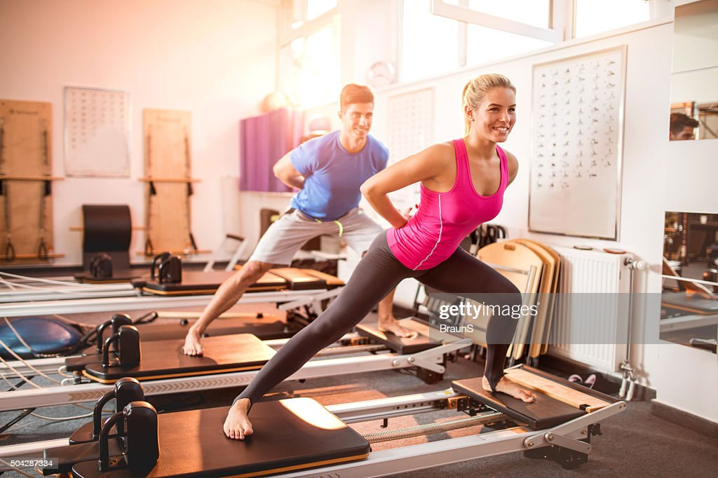 Two happy people exercising on Pilates machines in health club. : Stock Photo