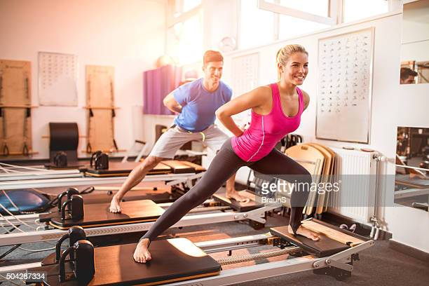 Two happy people exercising on Pilates machines in health club.