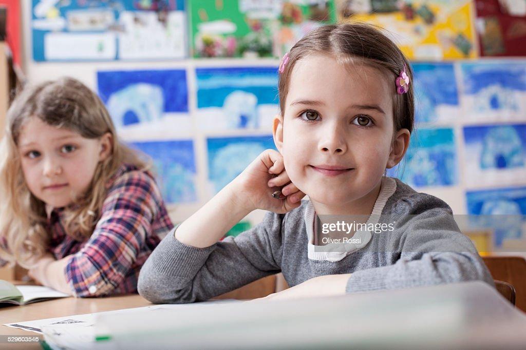 Two happy school girls (6-7) sitting in classroom : Bildbanksbilder
