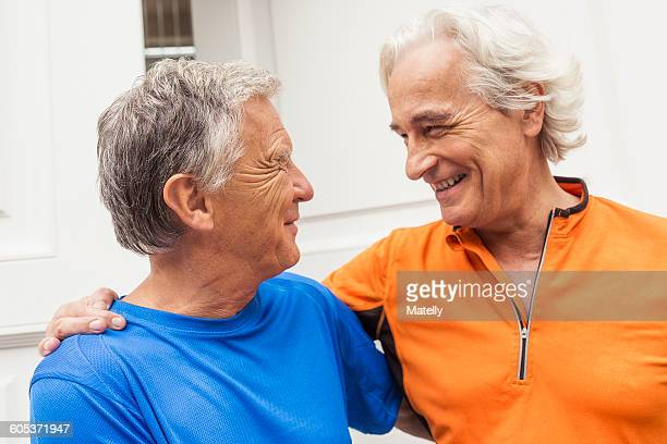 Two happy senior male runners at front door