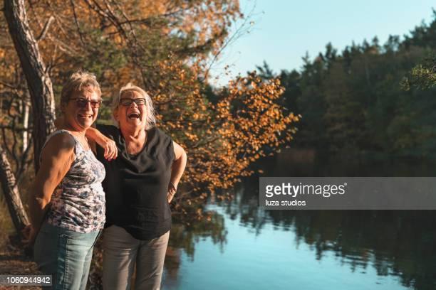 twee gelukkige senior vrouwen op een wandeling - noord europa stockfoto's en -beelden