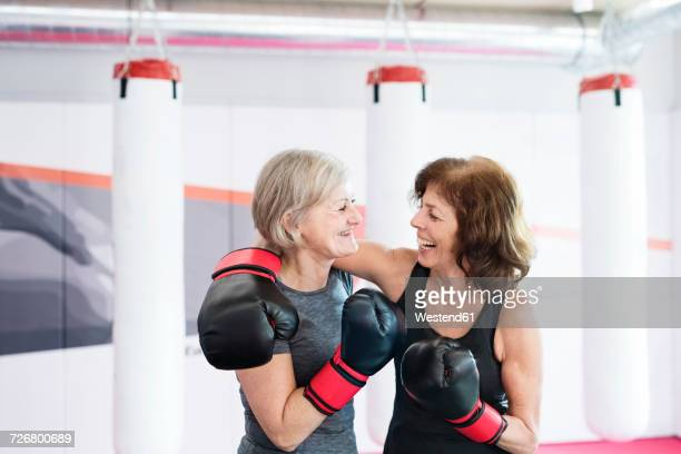 Two happy senior women with boxing gloves embracing in gym