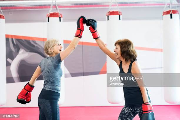 Two happy senior women with boxing gloves in gym