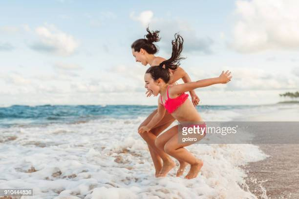 two happy sibling sisters jumping over waves