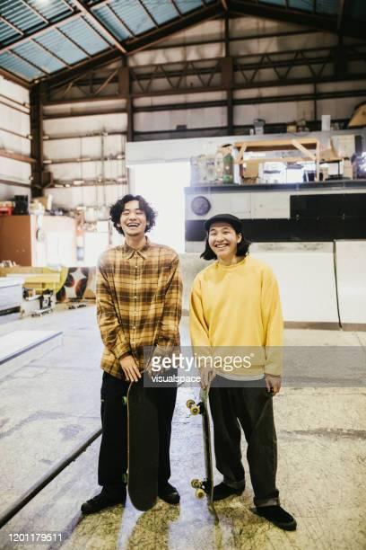 二人の幸せなスケートボーダー - minimalist living in japan ストックフォトと画像
