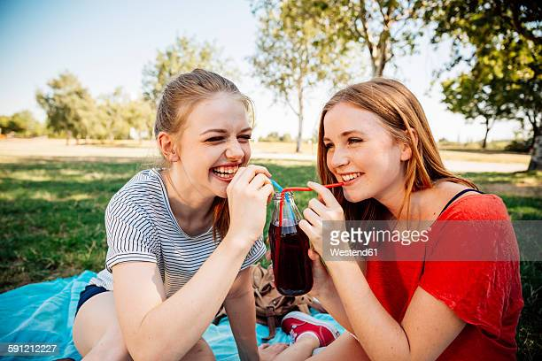 Two happy teenage girls sharing an ice tea in park