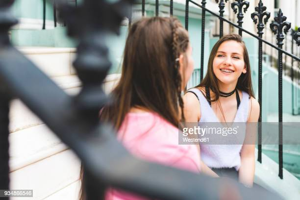 Two happy teenage sitting on stairs in the city talking