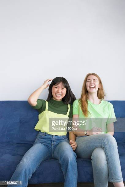 two happy teenagers sitting on sofa and laughing - showus stock pictures, royalty-free photos & images