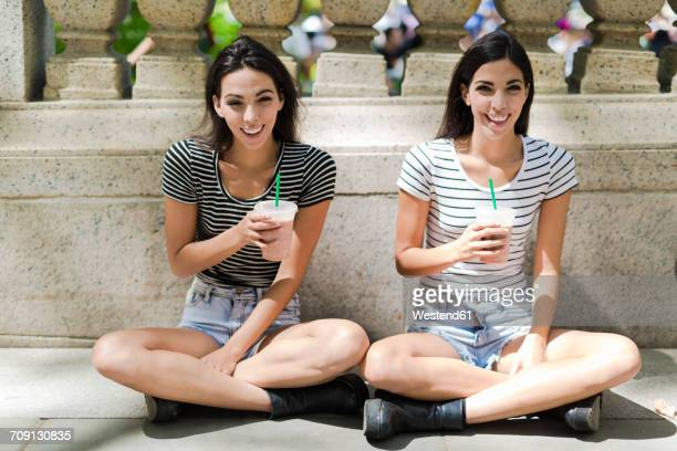 Two happy twin sisters sitting outdoors having a takeaway drink