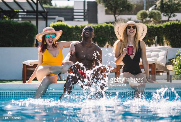 two happy women and a man sitting at the pool splashing with water - pool party stock pictures, royalty-free photos & images