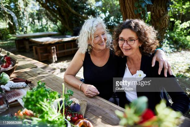 two happy women embracing at garden table - female friendship stock pictures, royalty-free photos & images