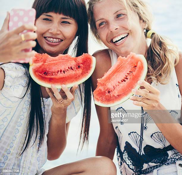 two happy women enjoying a day on the beach - brace stock pictures, royalty-free photos & images