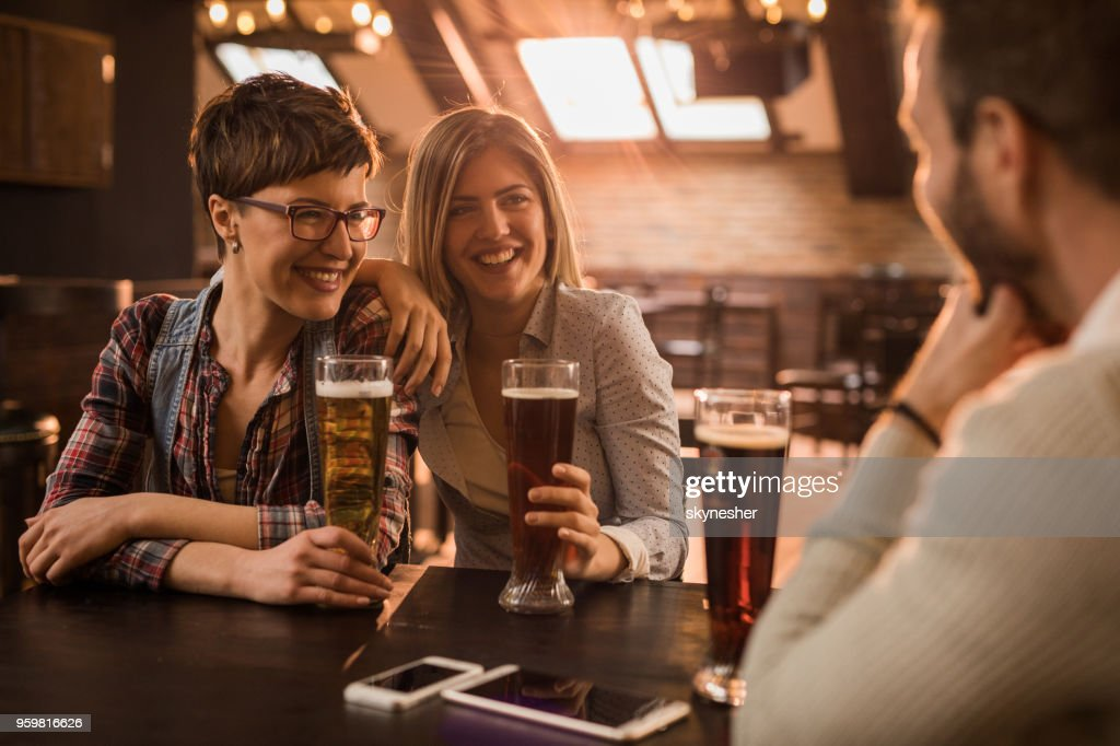 Zwei glückliche Frauen flirten mit einem Mann in einer Kneipe. : Stock-Foto