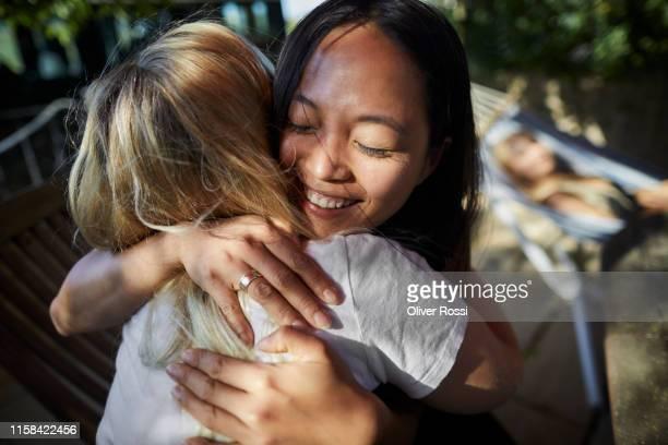 two happy women hugging outdoors - amicizia tra donne foto e immagini stock
