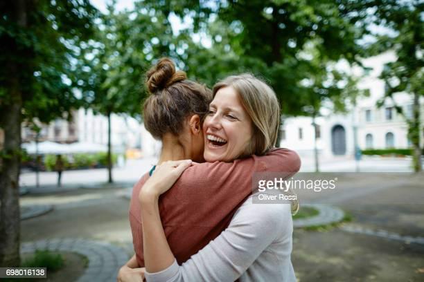 two happy women hugging outdoors - umarmen stock-fotos und bilder