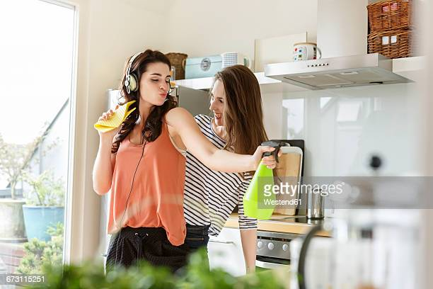 Two happy women in kitchen cleaning and listening to music