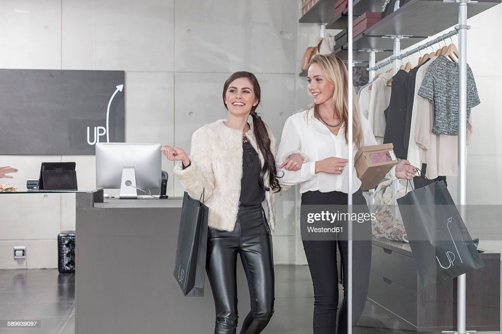 Two happy women shopping for clothes : Foto de stock