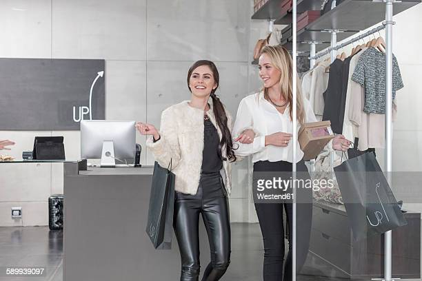 Two happy women shopping for clothes