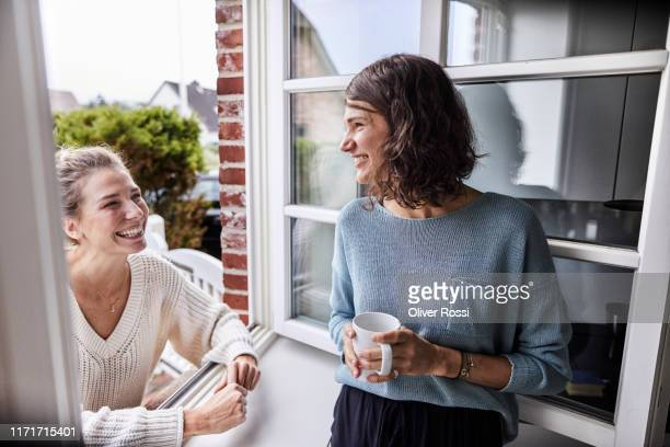 two happy women talking through the window - nur frauen stock-fotos und bilder