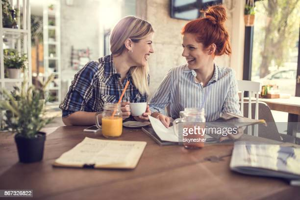 Two happy women talking while reading a magazine in a cafe.