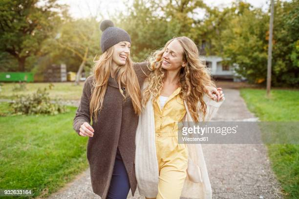 two happy women walking in rural landscape - freundschaft stock-fotos und bilder