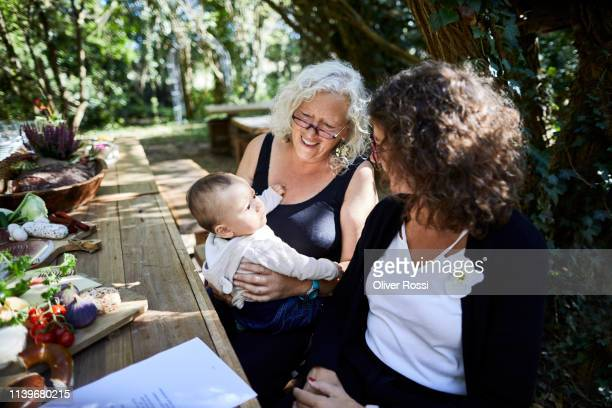 two happy women with baby sitting at garden table - linda oliver fotografías e imágenes de stock