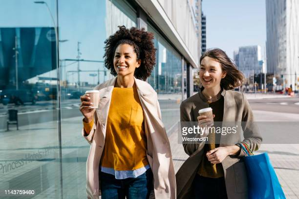two happy women with shopping bags and takeaway coffee walking in the city - 30 39 years stock pictures, royalty-free photos & images