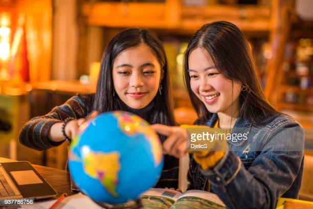 two happy young asian women exploring the globe. - korean teen stock pictures, royalty-free photos & images