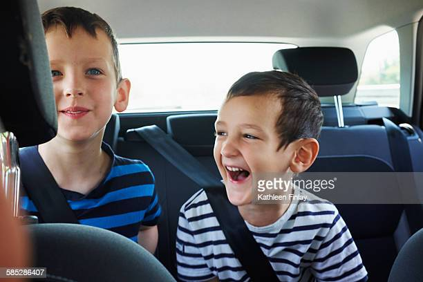 Two happy young brothers traveling in car back seat