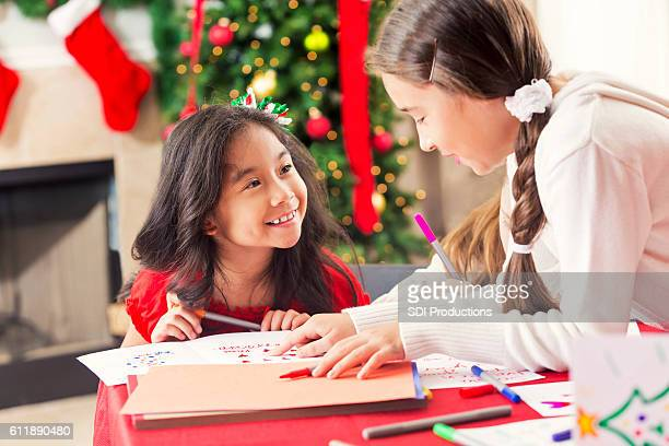 Two happy young girls making Christmas cards